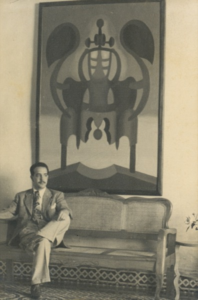 1946 - At his home in Matanzas, Cuba photographed with Flor a contra luz, 1943, oil on wood, 6x4